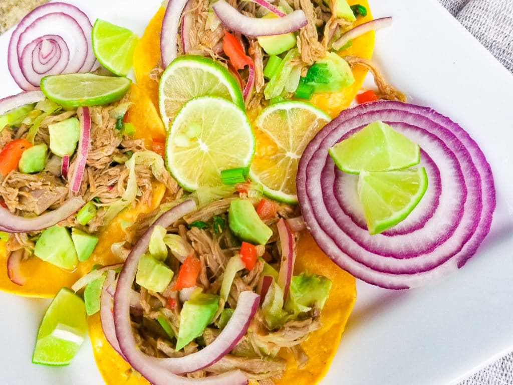 Salpicon de Res (Beef Salpicon) served on tostadas with lime wedges on a white platter.