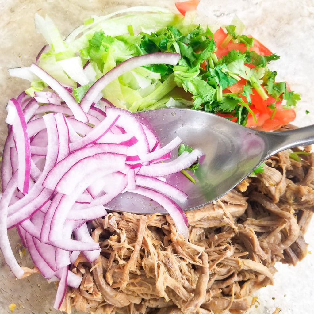 Shredded beef in a glass bowl with red onions, lettuce, tomatoes and seasonings for ensalada de salpicon.