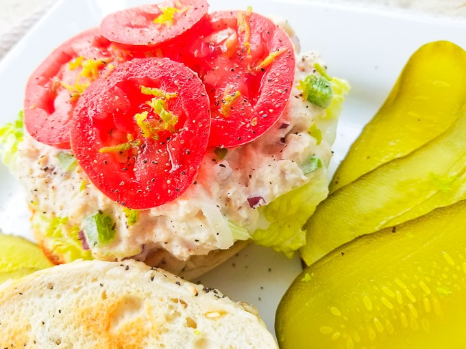 Sandwich de Atun (Tuna) served with a side of sliced pickles on a white platter.