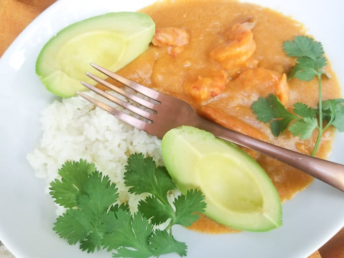 Sango de Camaron served with white rice and avocado slices, served in a white plate.