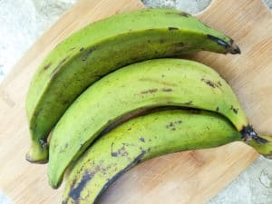 Whole Green plantains on a wooden cutting board.