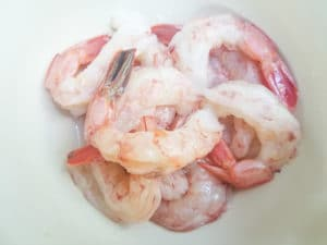 Peeled and deveined shrimp in a white bowl.