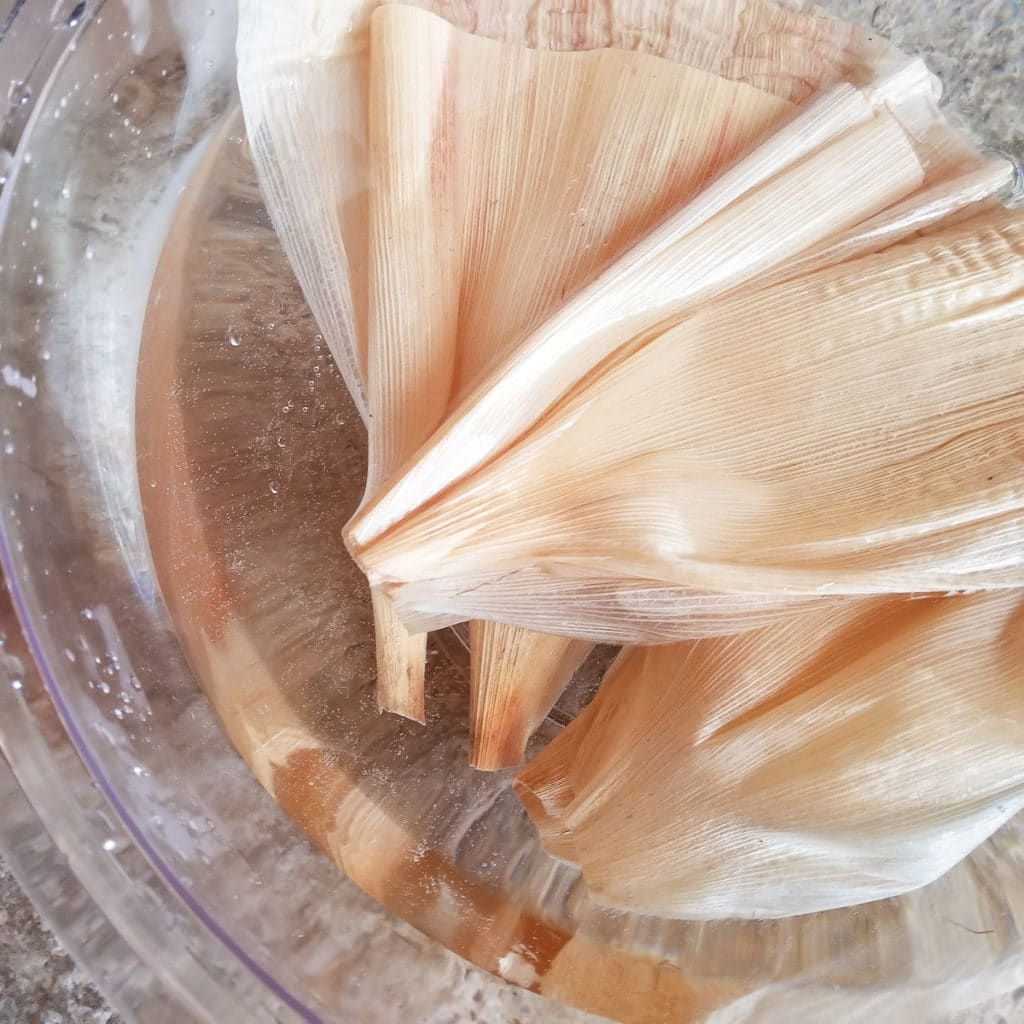 Corn husks added to a large bowl filled with water to soak husks.