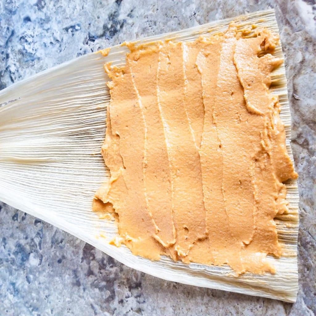 Tamale masa spread onto a corn husk for Tamales Rojos de Puerco (Chile Colorado Pork Tamales).