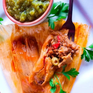 Cooked tamales served on a white platter with salsa verde and hot sauce.