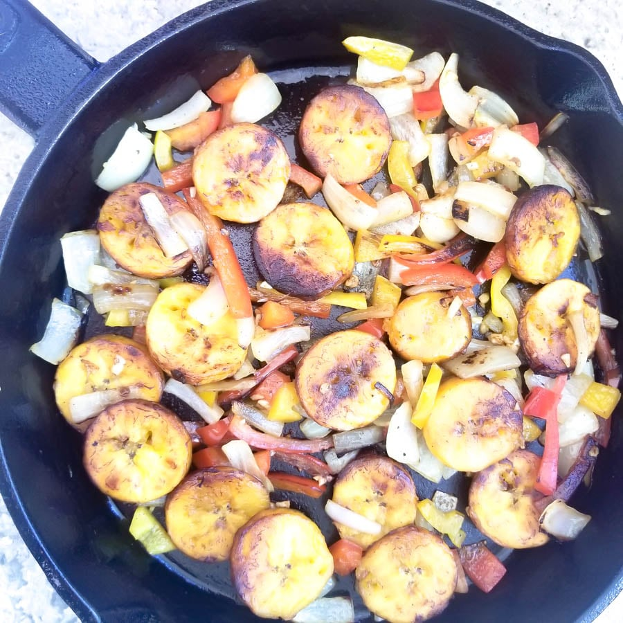 Veggies and cooked plantains in a cast iron skillet to make plantain omelette.